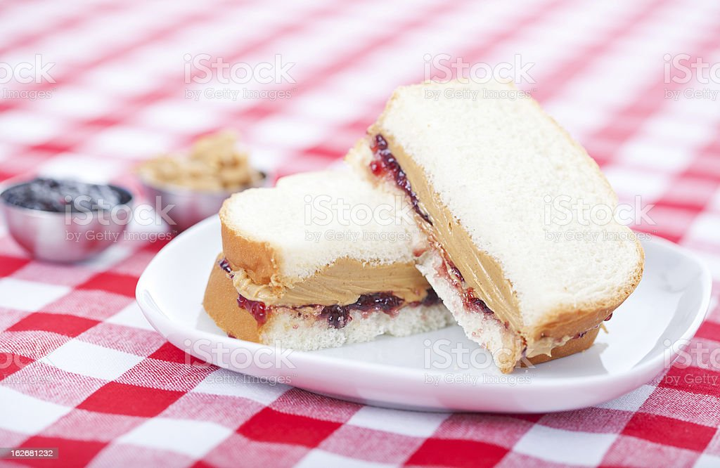 Peanut butter and jelly sandwich on red checkered tablecloth stock photo