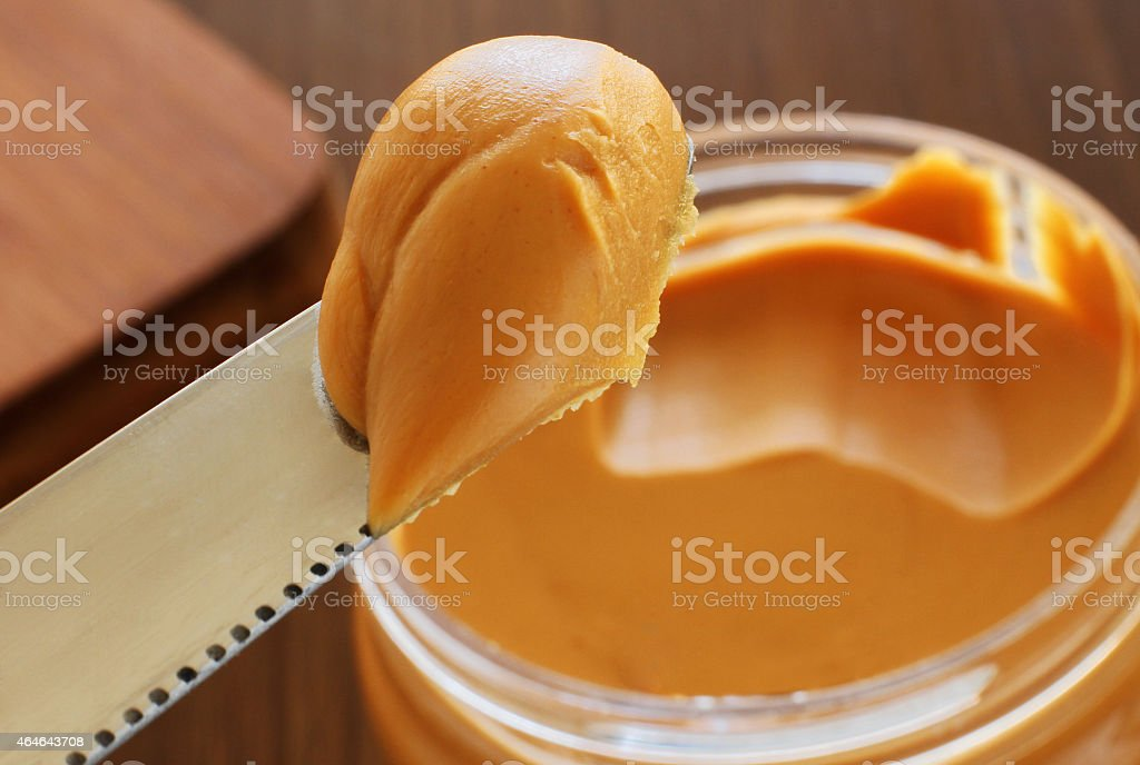Peanut butter jar and knife holding some of it stock photo