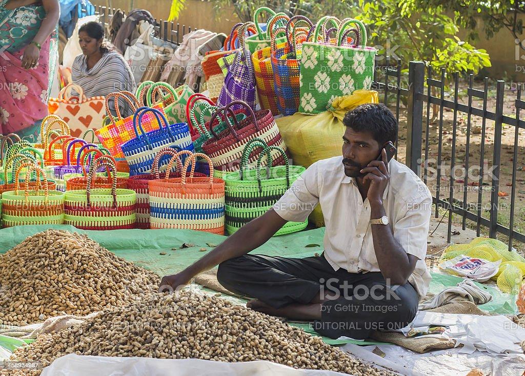 Peanut vendor using cellphone in Bangalore, India royalty-free stock photo