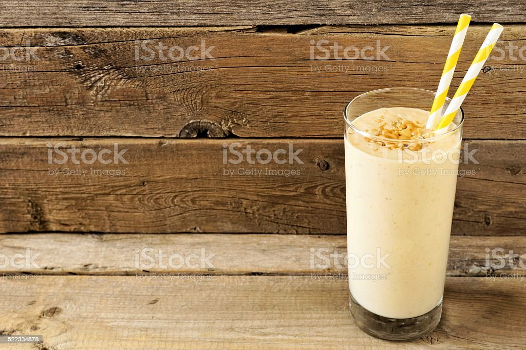 Peanut-butter banana oat smoothie with straws over rustic wood stock photo