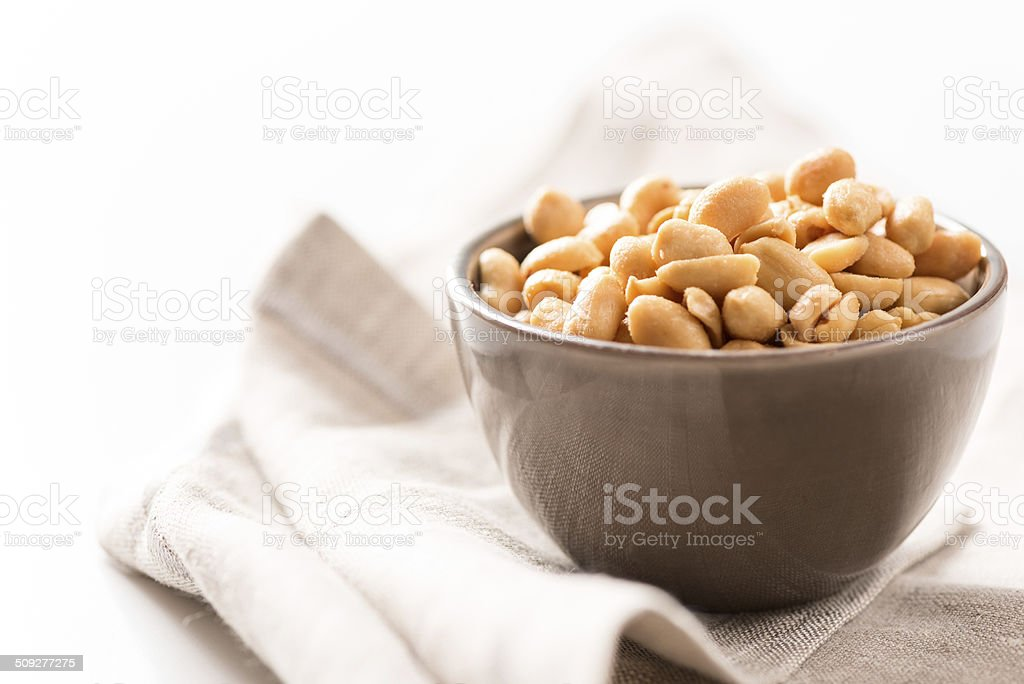 peanuts in a bowl on tablecloth horizontal stock photo