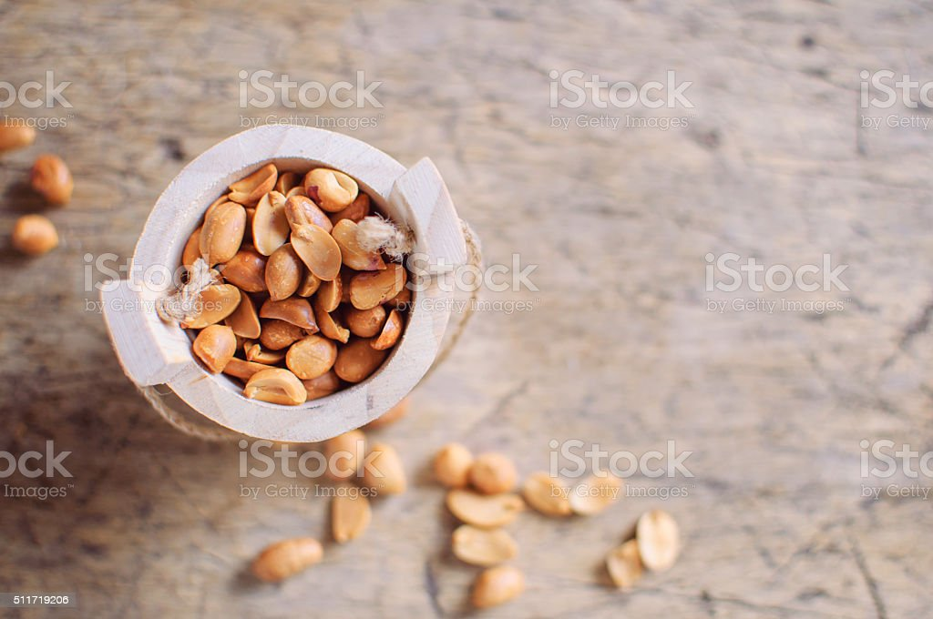 Peanuts in wooden bowl on wooden background stock photo