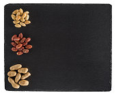 Peanuts on black slate board. Isolated on white background.