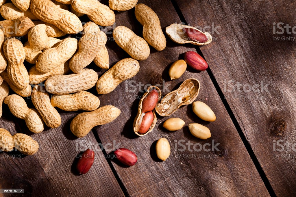 Peanuts on rustic wood table stock photo