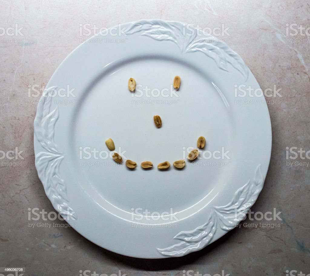 Peanuts on White Plate in Shape of a Smiling Face royalty-free stock photo
