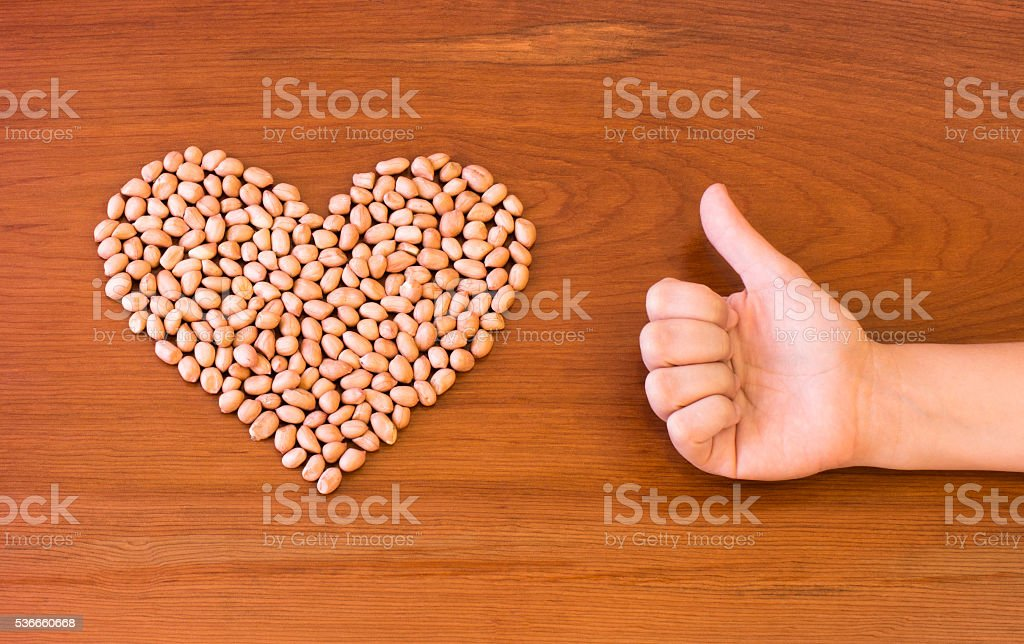 Peanuts shaped into a heart next to a thumbs up. stock photo