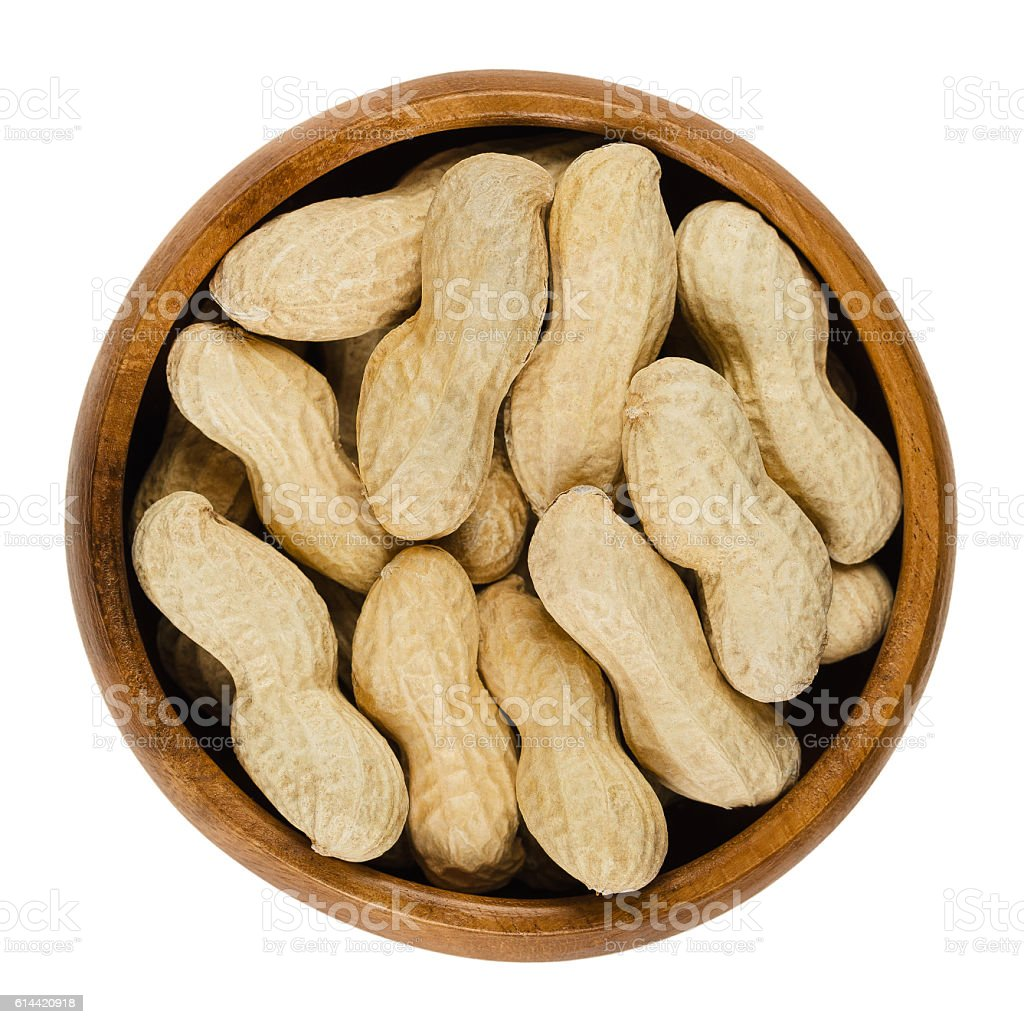 Peanuts with shell in wooden bowl over white stock photo