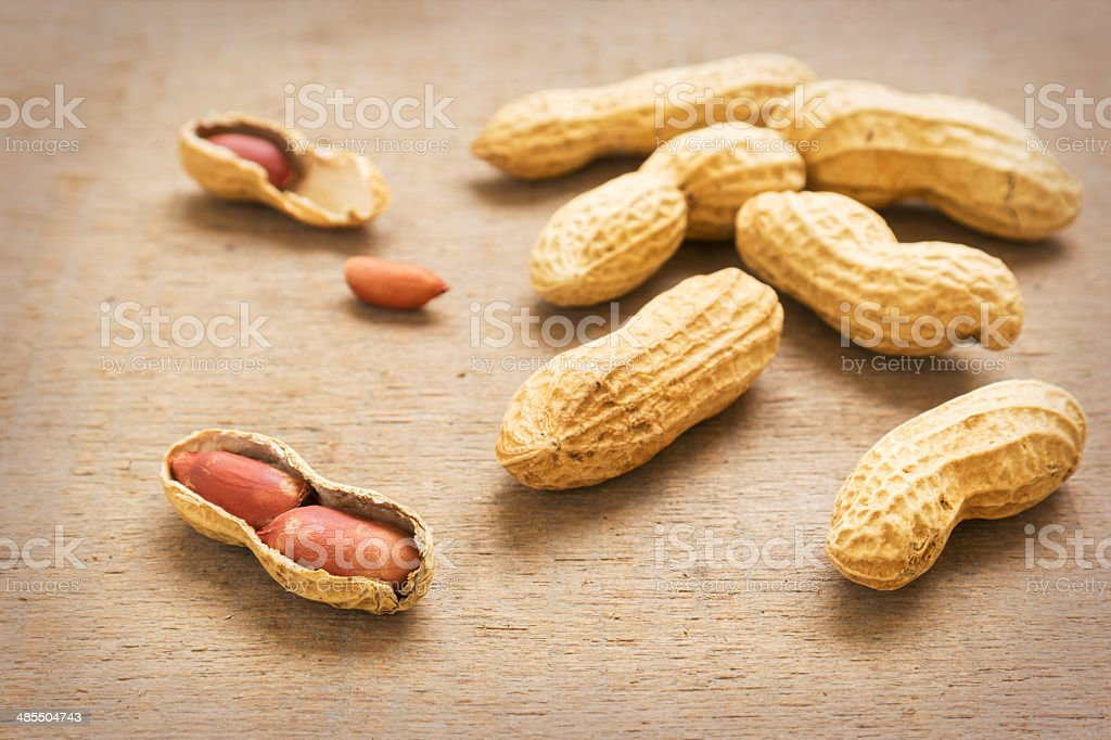 Peanuts with shells on wooden table stock photo