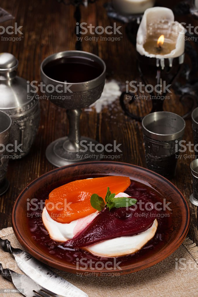 pear in white and red wine sauce stock photo