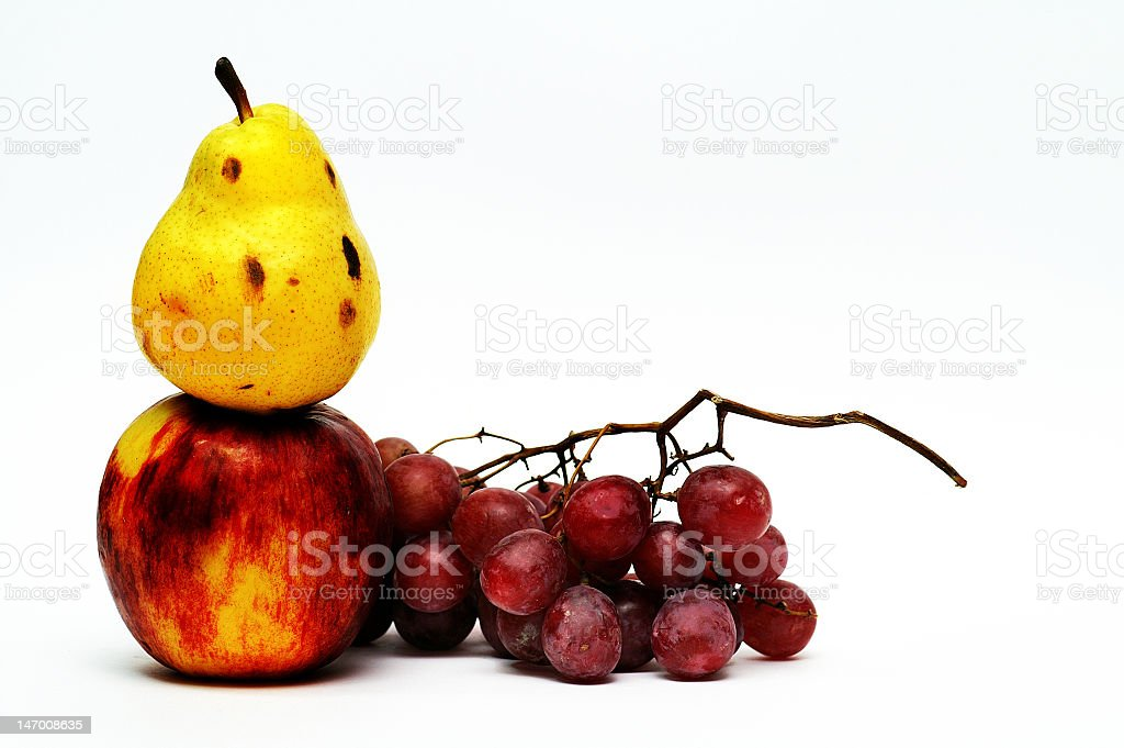 Pear on top of apple and red grapes royalty-free stock photo