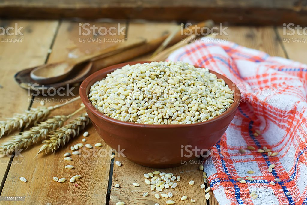 Pearl barley in a ceramic bowl on a wooden background.selective stock photo