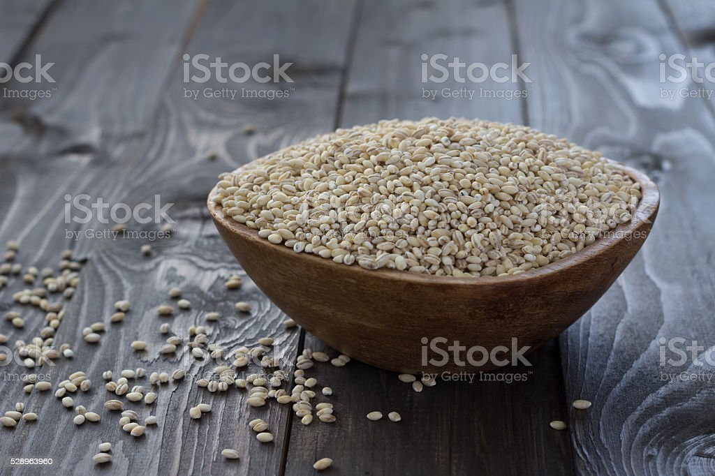 Pearl barley in a wooden bowl stock photo