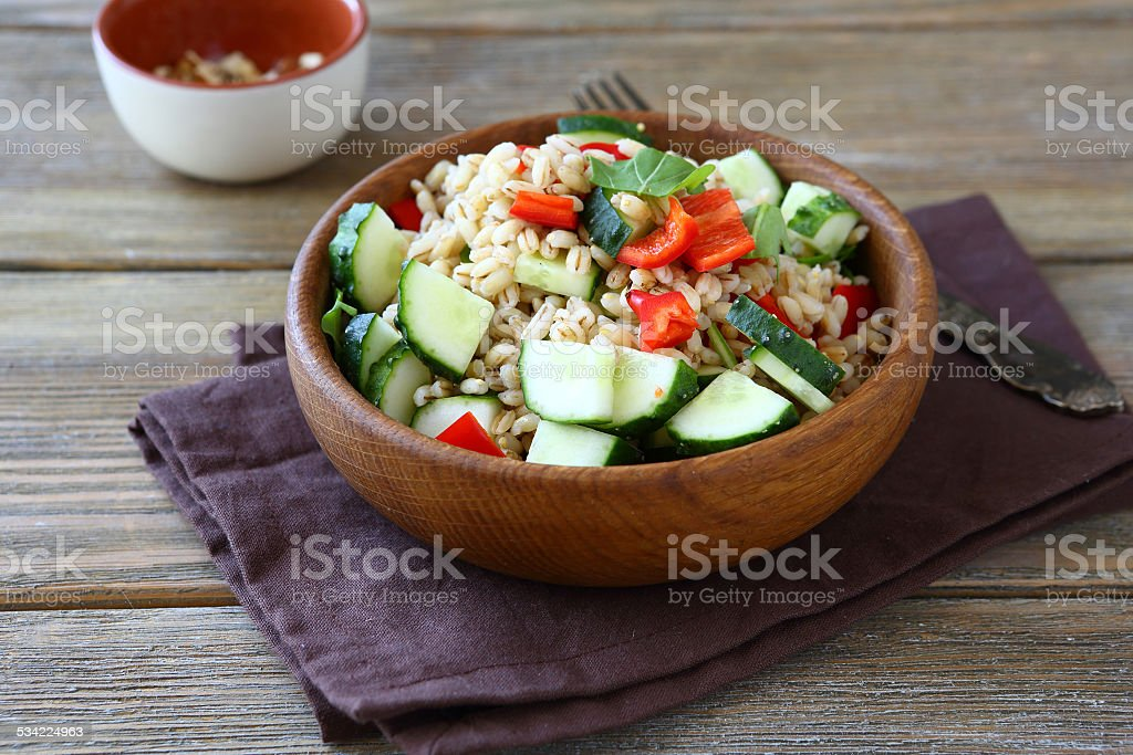 Pearl barley salad with vegetables in a wooden bowl stock photo