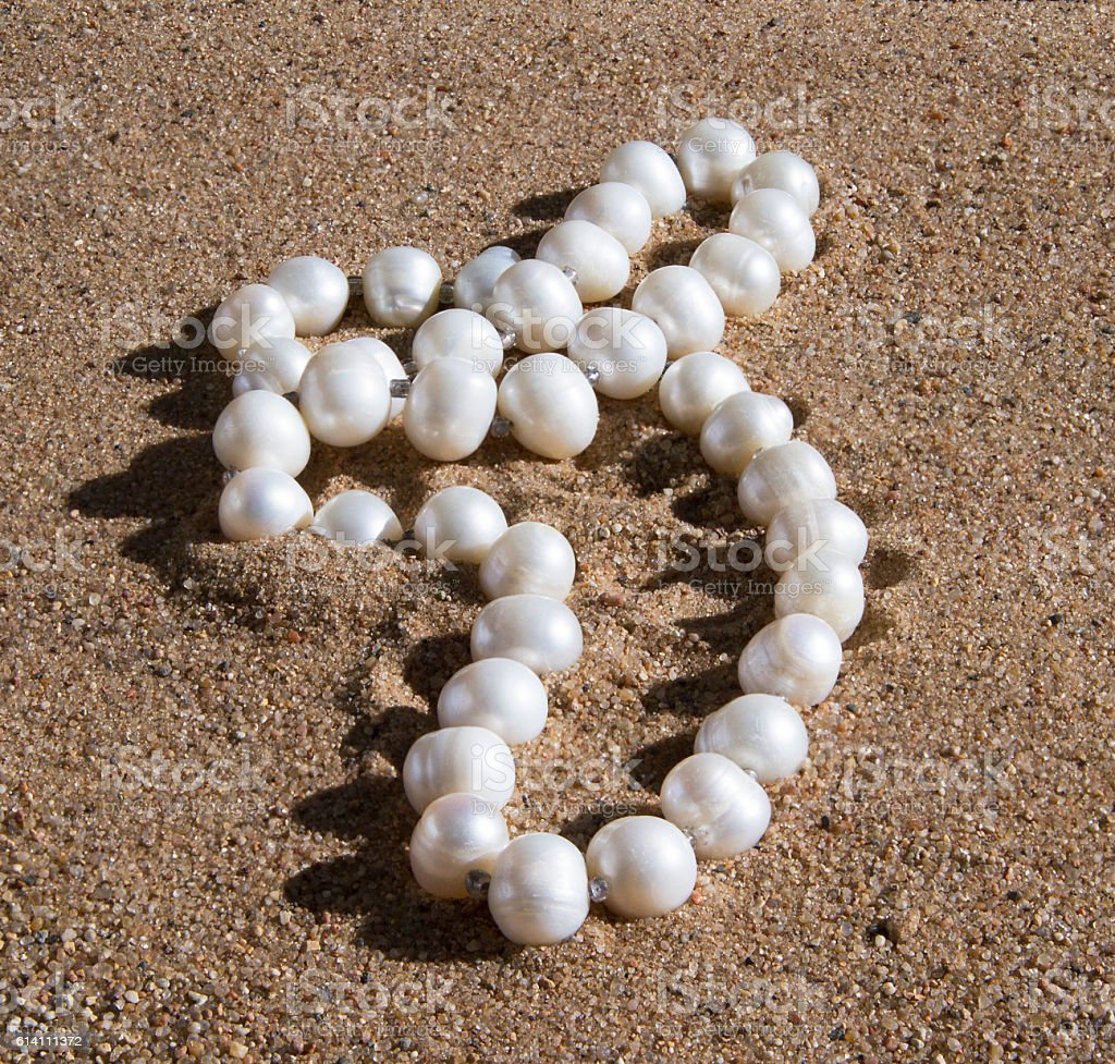 pearl beads lying on the sand stock photo