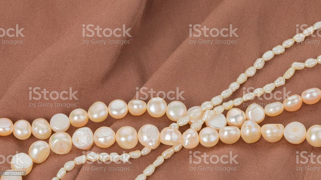 pearl beads on brown cloth stock photo