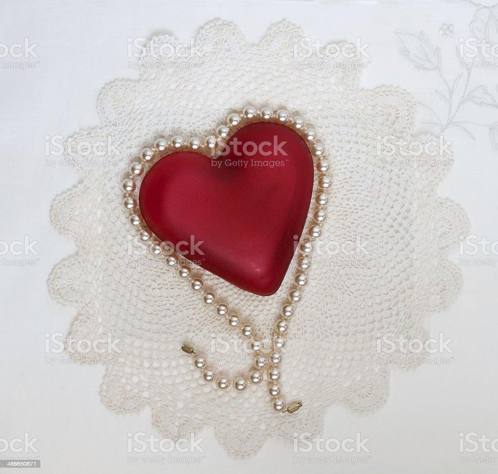Pearl Draped Heart on Doily royalty-free stock photo