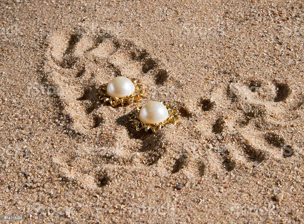pearl earrings in gold lying on the sand stock photo