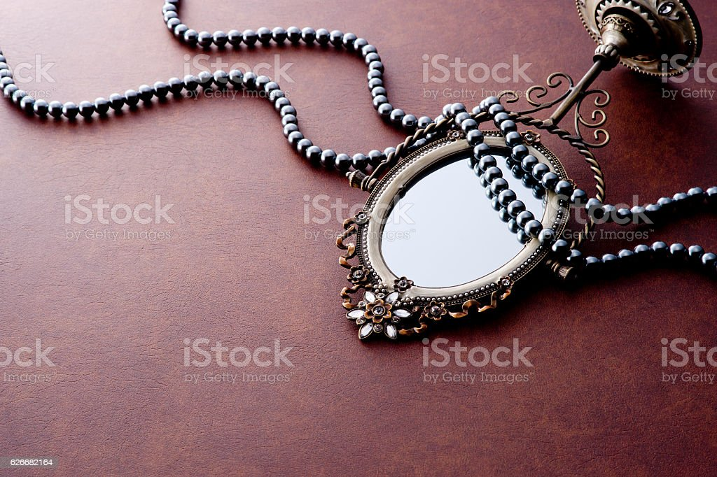 Pearl jewellery and mirror on brown background stock photo