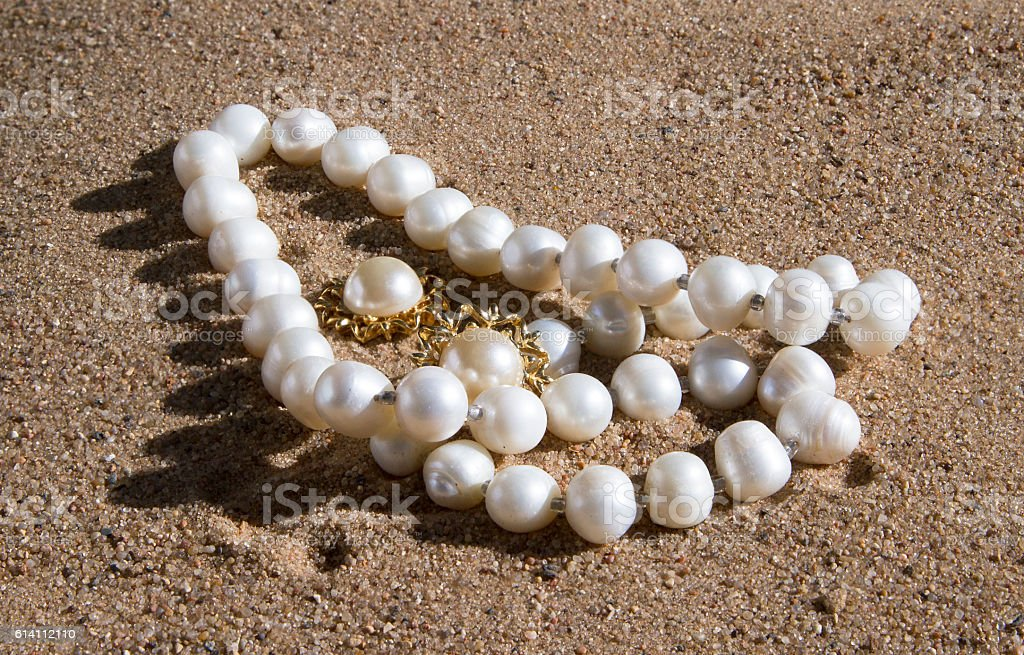 pearl necklace and earrings lying on the sand stock photo