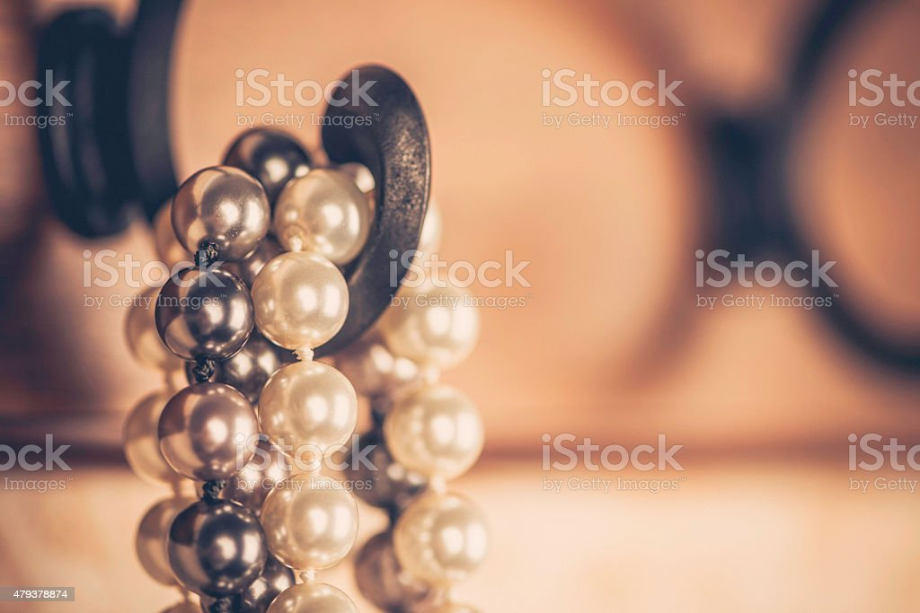 Pearl necklaces hanging on coat rack. Vintage toned stock photo
