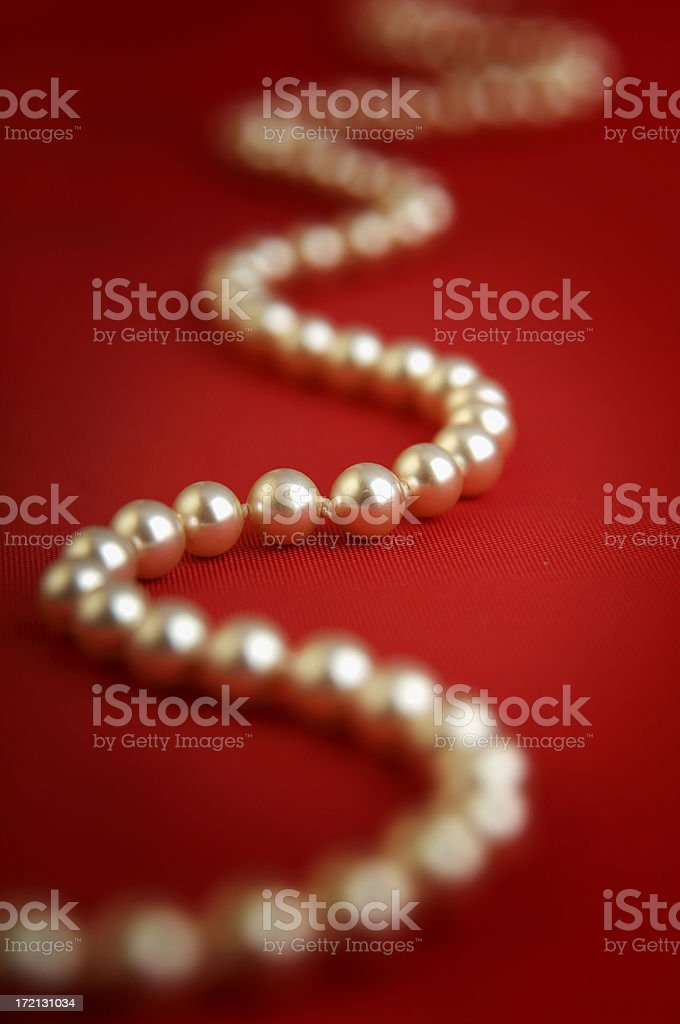 Pearls on a red background royalty-free stock photo