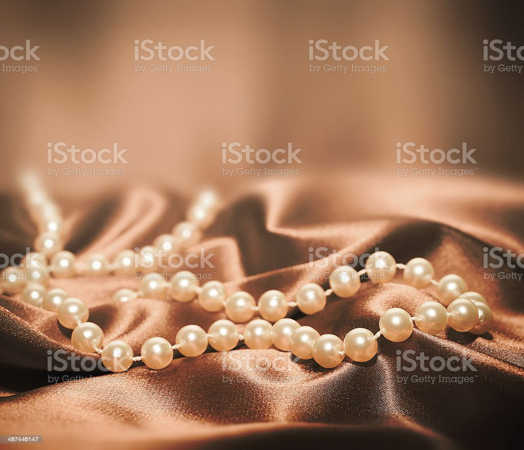 Pearls on a silk fabric background stock photo