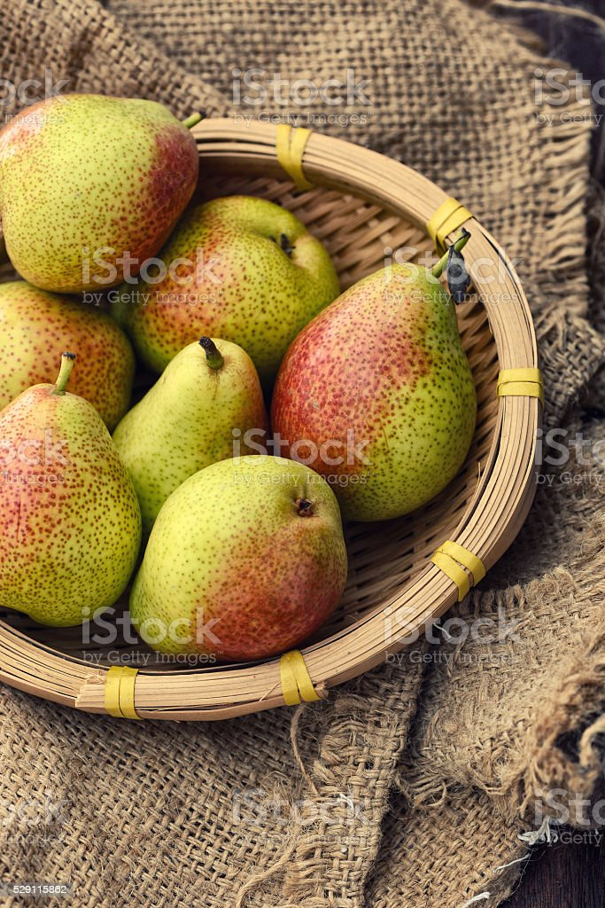 pears in a basket on a hessian background stock photo