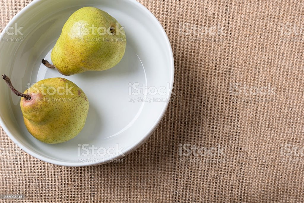 Pears in a bowl on burlap stock photo