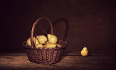 Pears in a wicker basket on dark painting background.