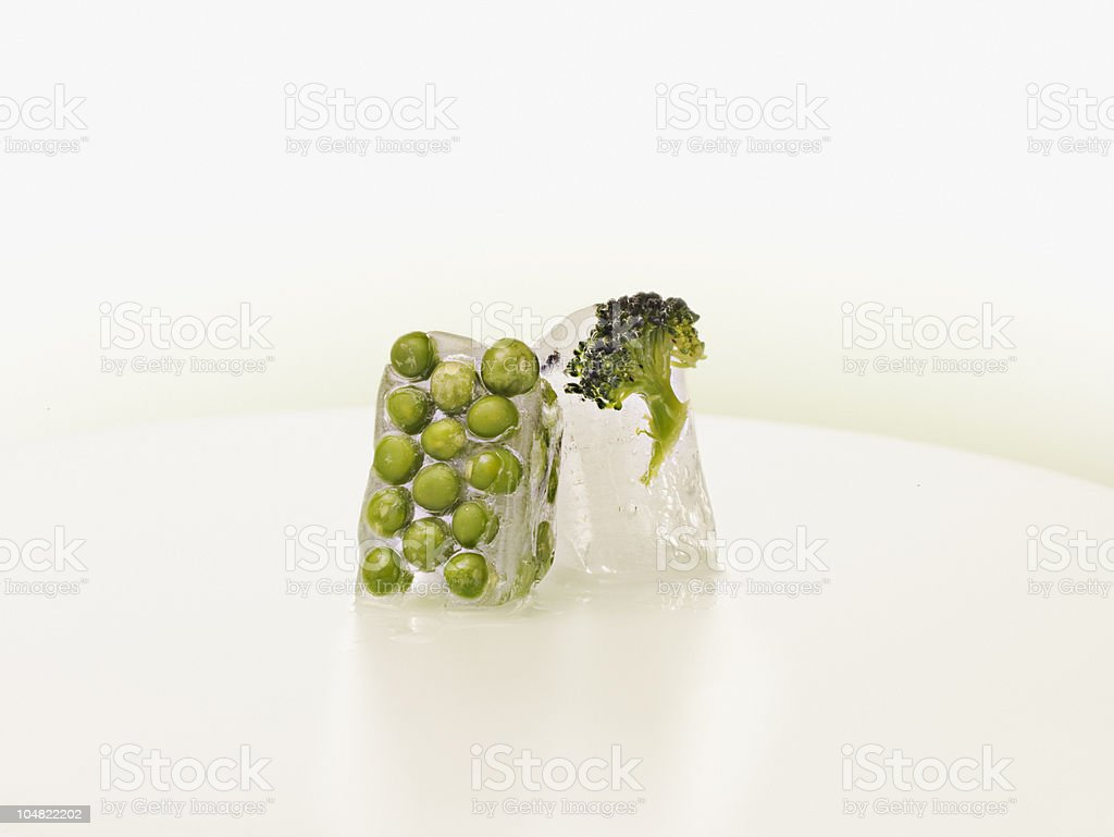 Peas and broccoli frozen in ice cubes royalty-free stock photo