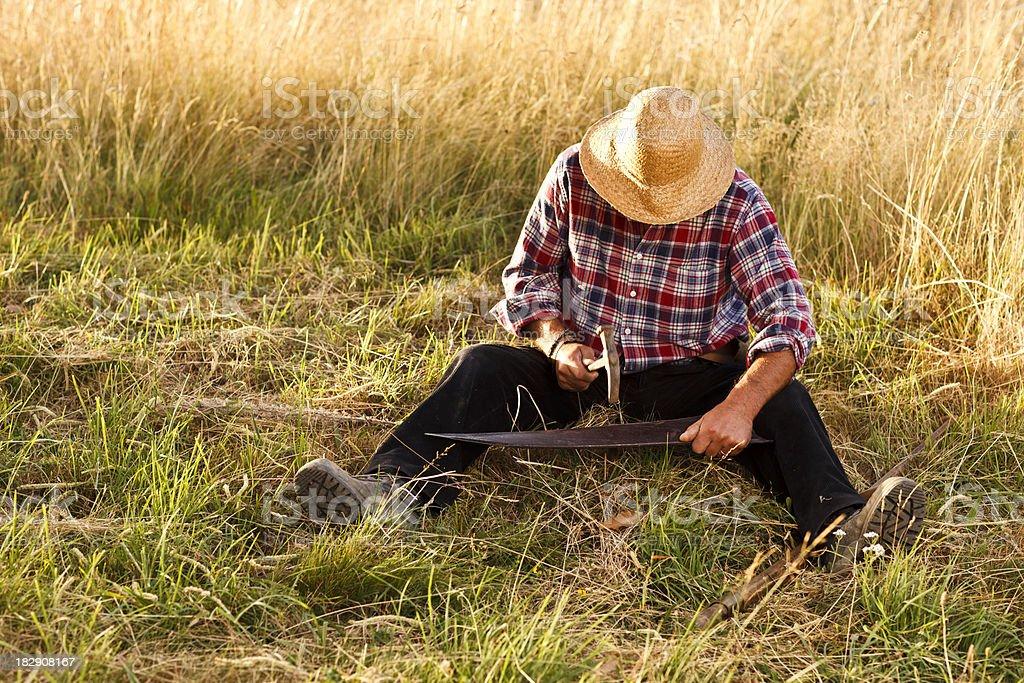 Peasant fixing a scythe stock photo
