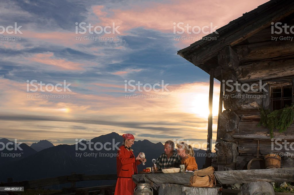 Peasant woman serving couple at alpine hut stock photo