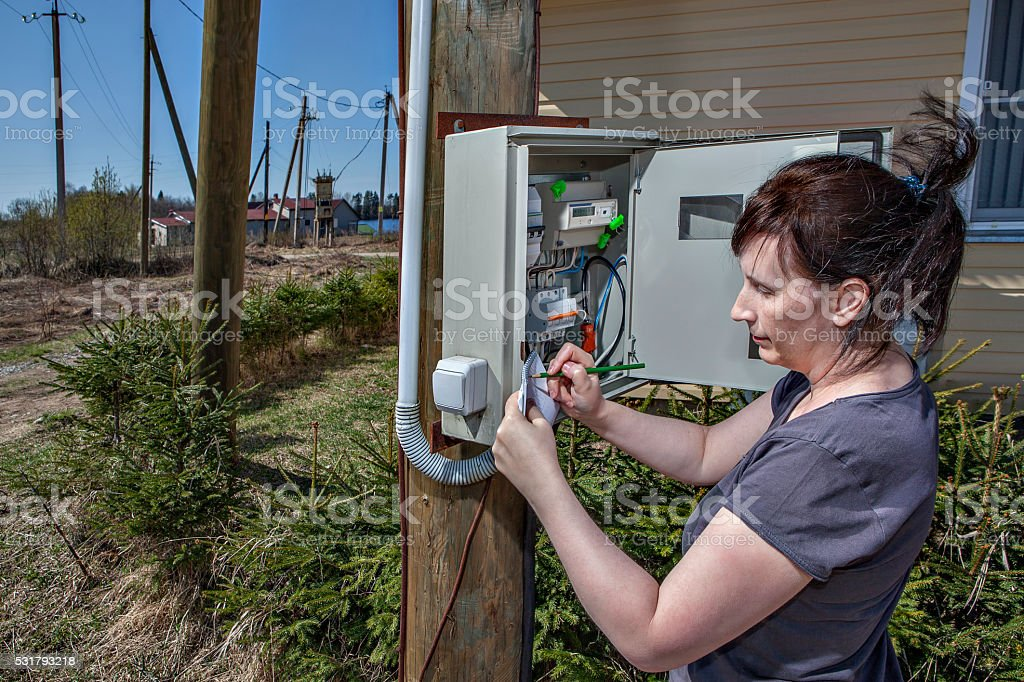 Peasant Women writing down electric  meter reading in fuse box stock photo