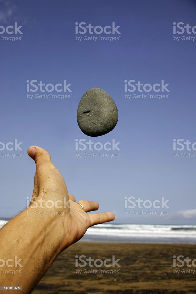 Pebble and Hand on the Beach royalty-free stock photo