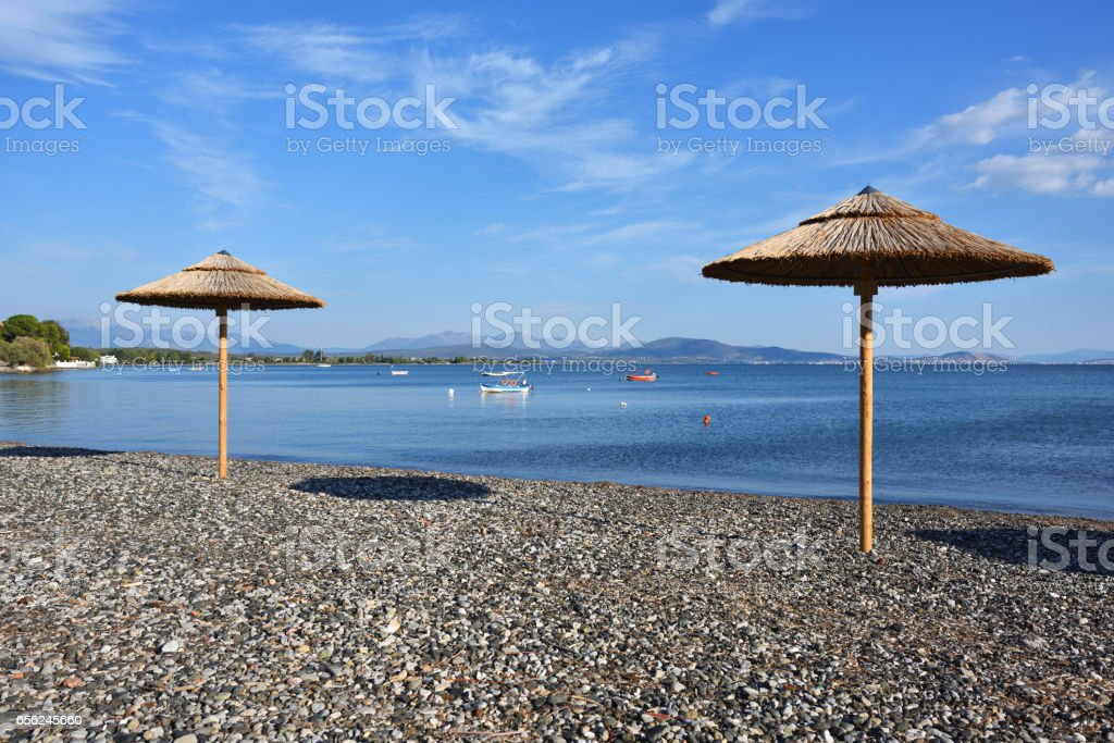 Pebble beach and parasols in Greece stock photo