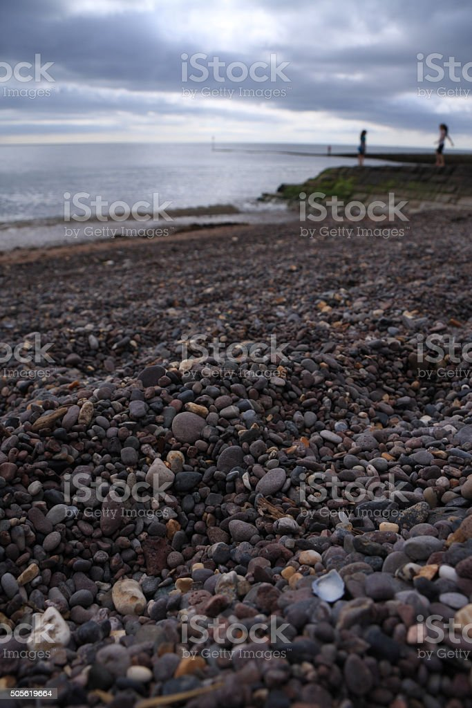 Pebble beach with blurred shapes of children playing stock photo