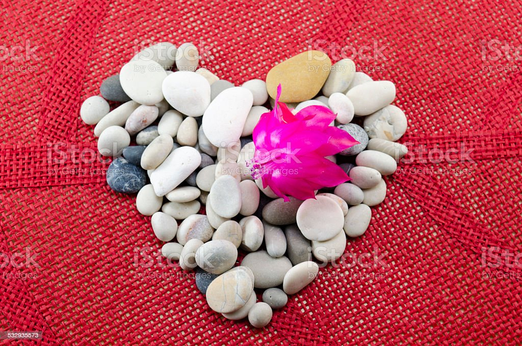 Pebble heart decorated with a pink flower royalty-free stock photo