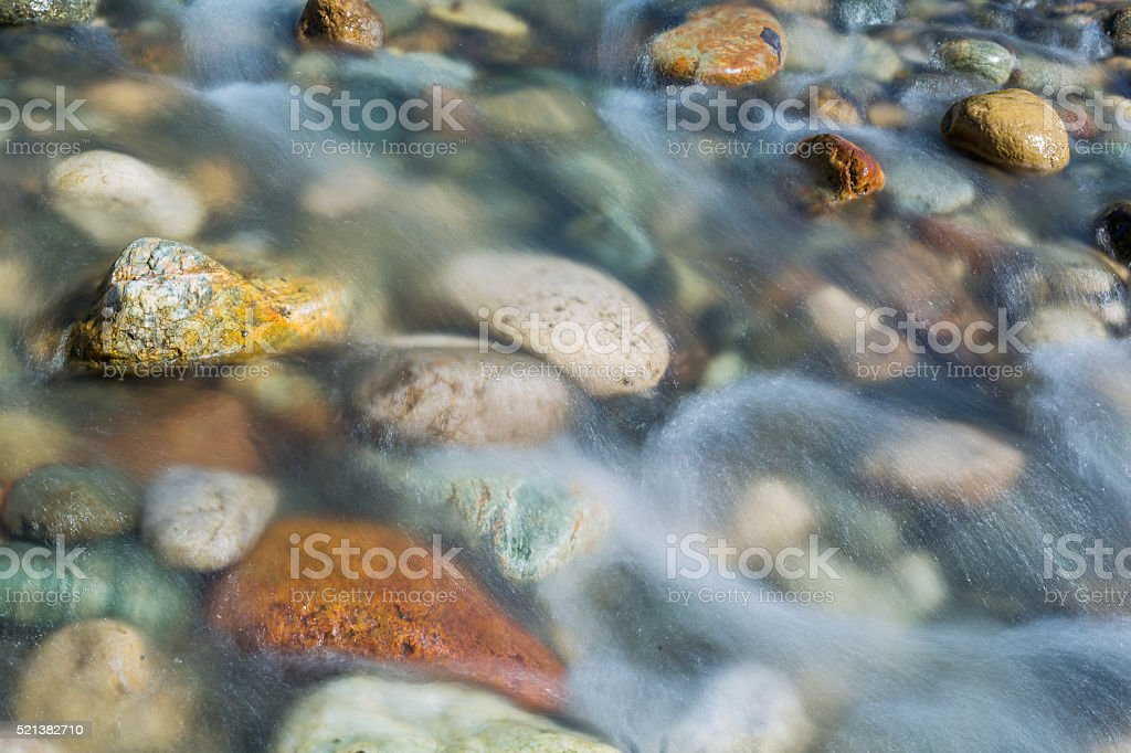 Pebble stones in the river water close up view, stock photo