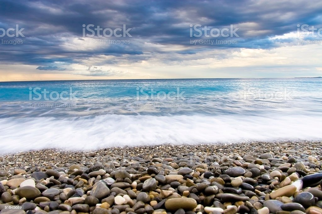 Pebbled beach and a bright blue sea royalty-free stock photo