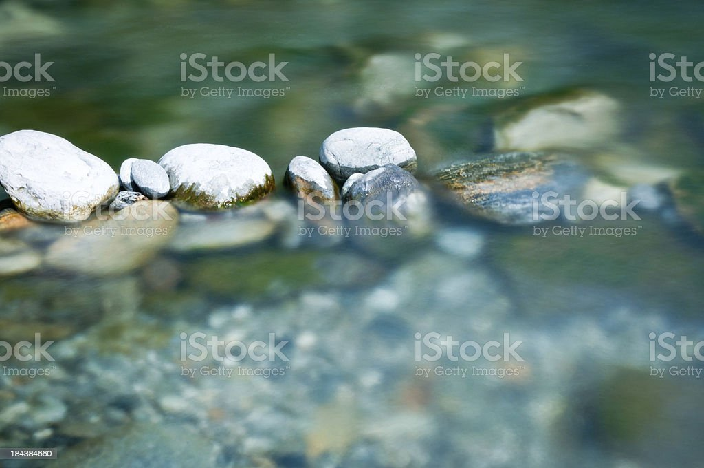 Pebbles and arranged stones in river water stock photo
