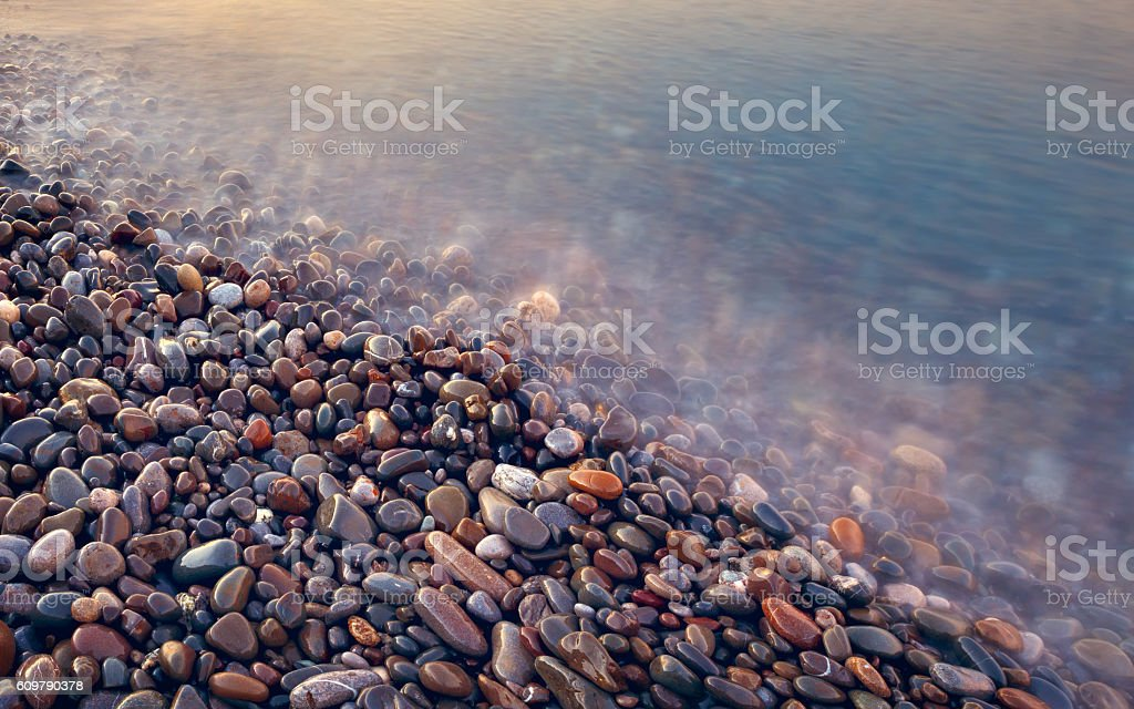 pebbles in sea vintage style long exposure abstract background stock photo