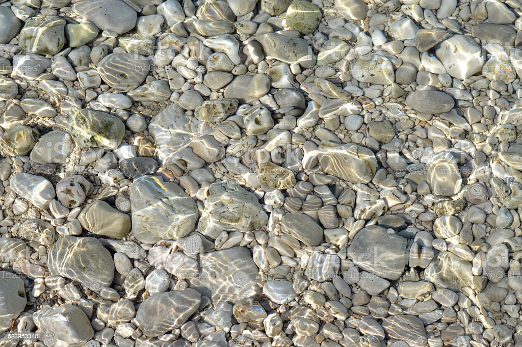 Pebbles in the clear water stock photo