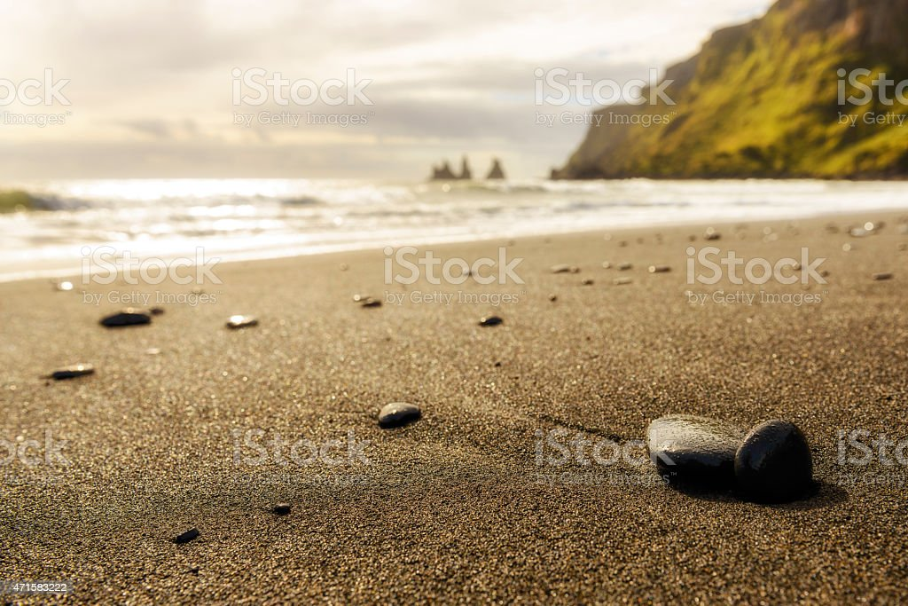 Pebbles on a black beach in a sunset in Iceland stock photo