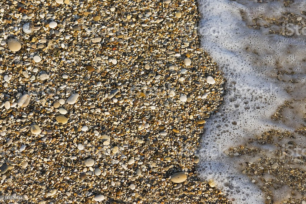 Pebbles on the beach with foam royalty-free stock photo