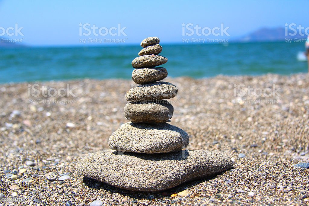 Pebbles pied up as tower on beach stock photo