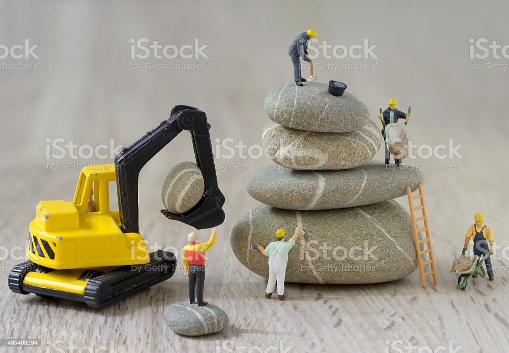 Pebbles stack and figurines workers stock photo