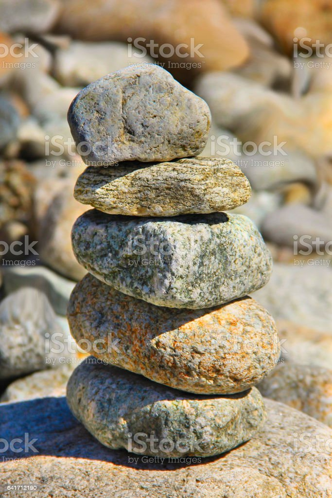 pebbles tower in the river bank closeup stock photo