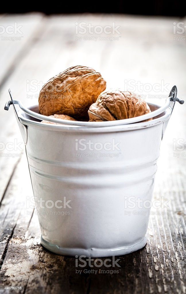 pecan nuts in a bucket on wooden background stock photo