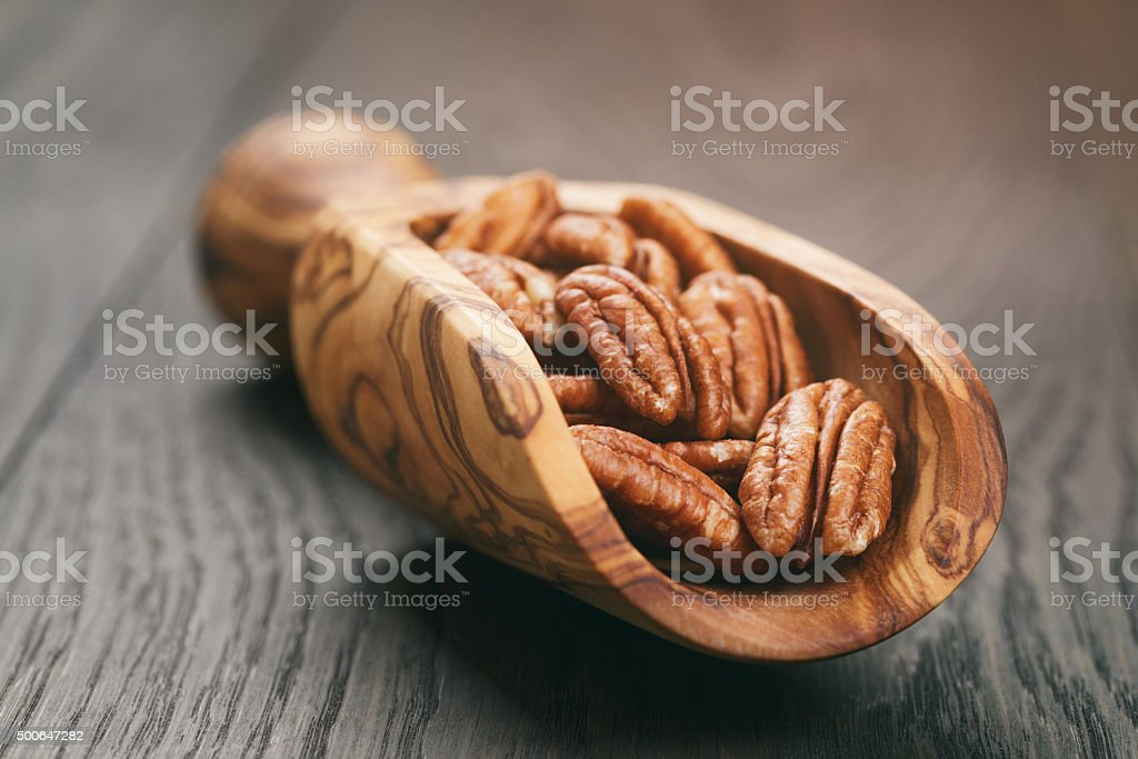 pecan nuts in olive wood scoop on oak table stock photo