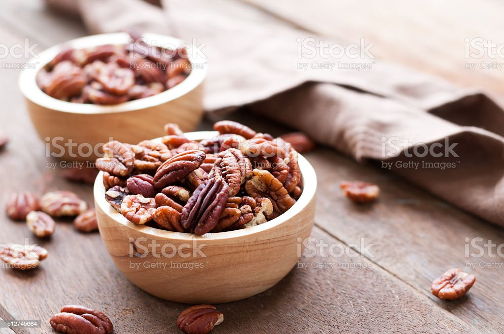 Pecan nuts in wooden bowel on wooden stock photo